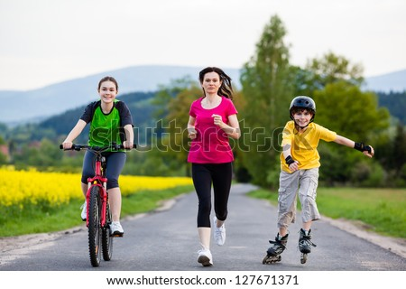 Active family - mother and kids running, biking, rollerblading - stock photo