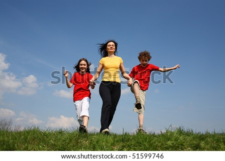 Active family - mother with kids running on green meadow