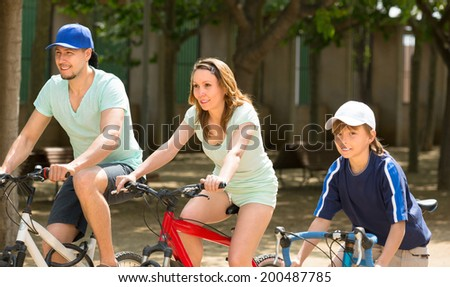 Active family riding bikes in the park summer day - stock photo