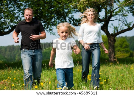 Active family running down a meadow with dandelion flowers at a bright spring day, playing tag or just enjoying themselves - stock photo