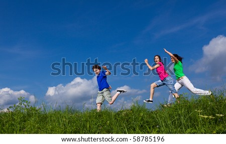 Active family running outdoor against blue sky - stock photo