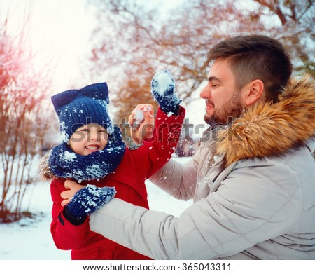 active father and son playing snowballs in winter park - stock photo