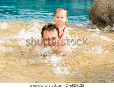 Active father teaching his toddler daughter to swim in pool on tropical resort . Summer vacations and sport  concept - stock photo