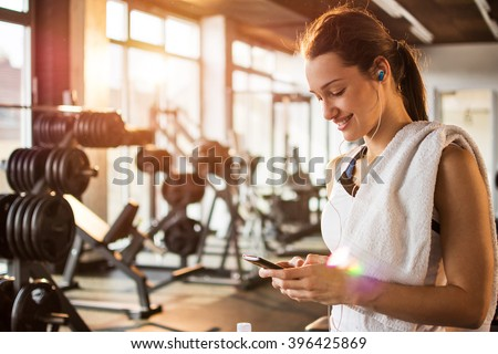Active girl using smartphone in fitness gym. - stock photo
