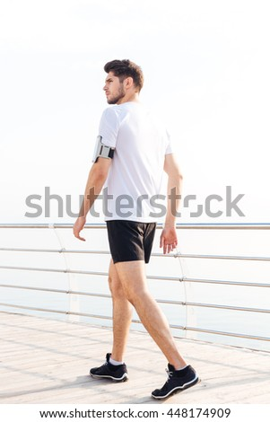 Active handsome young sportsman with armband walking on pier - stock photo