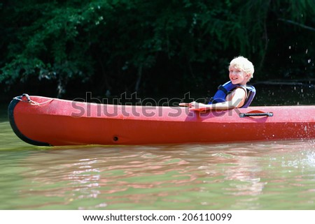 Active happy child, teenage school boy, having fun enjoying adventurous experience kayaking on the river on a sunny day during summer vacation - stock photo