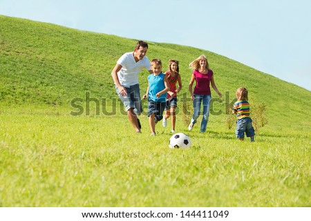 Active happy family playing with a ball - stock photo