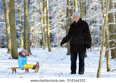 Active happy healthy grandfather and his little toddler granddaughter wearing colorful snowsuit enjoying a sledge ride in a beautiful snowy forest on sunny winter day - stock photo