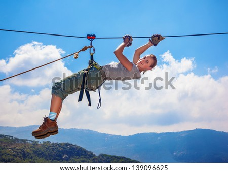 Active happy woman overhanging on tightrope in the mountains on blue sky background, climbing sport, mountaineering adventure, summer trekking concept - stock photo