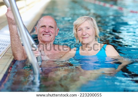 Active healthy happy senior couple having fun together in the swimming pool - stock photo