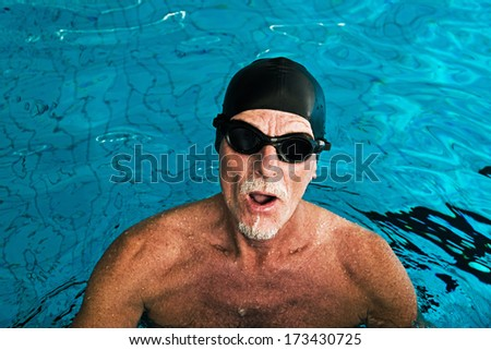 Active healthy senior man with beard in swimming pool wearing black cap and glasses.