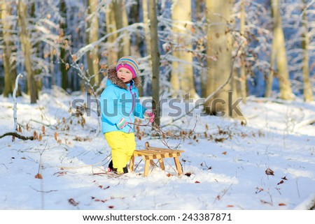 Active healthy toddler girl wearing colorful snowsuit and bright knitted hat and mittens enjoying snow playing with sledge in a beautiful snowy forest on sunny winter day - stock photo