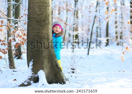 Active healthy toddler girl wearing colorful snowsuit and bright knitted hat playing and hiding behing tree in a beautiful snowy forest on sunny winter day - stock photo