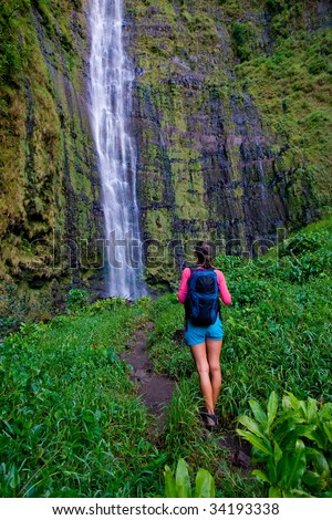 active healthy woman on hike to waterfall with backpack in hana maui, hawaii - stock photo