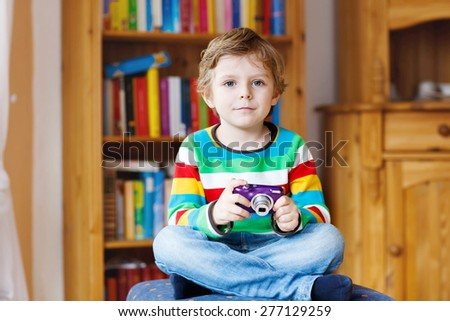 Active kid boy holding photocamera in hands, indoors. Child wearing colorful shirt. Portrait in a daycare. - stock photo