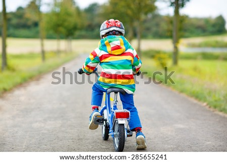 Active kid boy in safety helmet and colorful clothes on bike on summer day. Active leisure for children outdoors. - stock photo