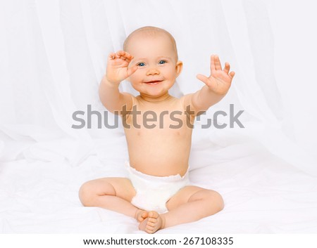 Active laughing baby sitting in diapers and having fun on the bed at home - stock photo