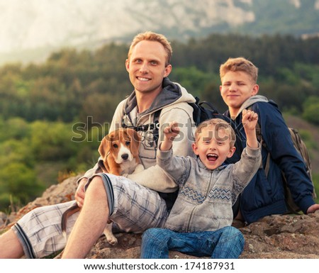 Active leisure - father with sons on mountain walk - stock photo