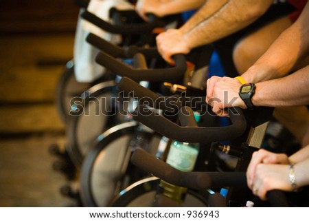 Active Lifestyle - Men & women pedalling on stationery bikes - Shallow DOF Focus on the hand with the watch