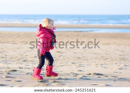 Active little child, laughing cute toddler girl wearing warm pink coat and pretty shoes playing with sand running on the beach of North Sea on sunny winter or spring day - stock photo