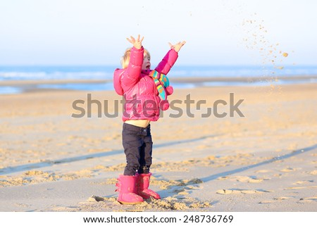 Active little child, laughing cute toddler girl wearing warm pink coat and pretty shoes playing on the beach of North Sea on sunny winter or spring day - stock photo