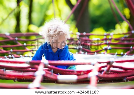 Active little child playing on climbing net and jumping on trampoline at school yard playground. Kids play and climb outdoors on sunny summer day. Funny boy on nest swing at preschool sport center. - stock photo