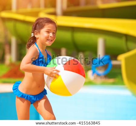 Active little girl playing with ball near pool, having fun in aquapark, water amusement, enjoying summer holidays, happiness concept - stock photo