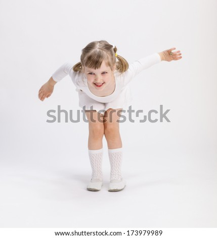 Active little girl training on white background