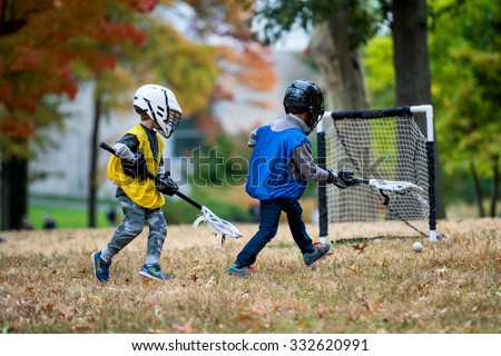 Active little kids playing lacrosse  - stock photo