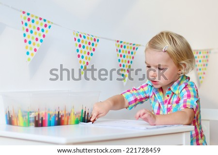 Active little preschool age child, cute toddler girl with blonde curly hair, drawing picture on paper using colorful pencils and felt-tip pens, sitting at white table indoors at home or kindergarten - stock photo