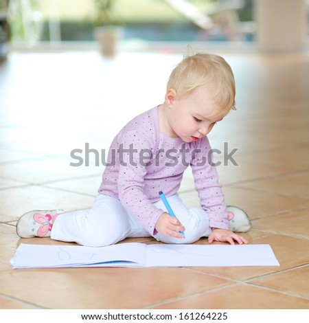 Active lovely baby girl plays indoors drawing with colorful pencils sitting on tiles floor - stock photo