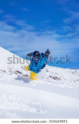 Active male in snowboard outfit jumping in snow - stock photo