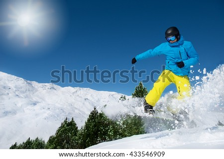 Active man in ski outfit riding down the slope
