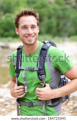 Active man portrait of sporty guy hiking outdoors. Young male hiker smiling happy at camera wearing backpack outdoors during hike in forest nature. Caucasian male model outside. - stock photo