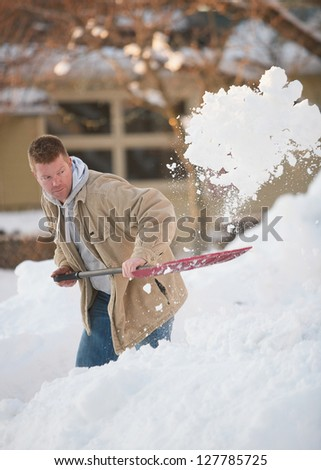 Active man shoveling snow in winter - stock photo