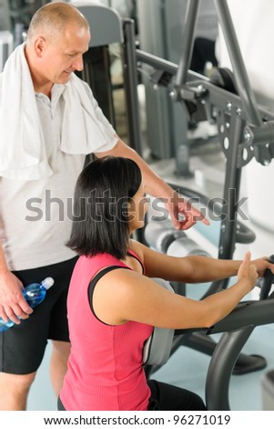 Active man watch personal trainer show exercise on gym machine