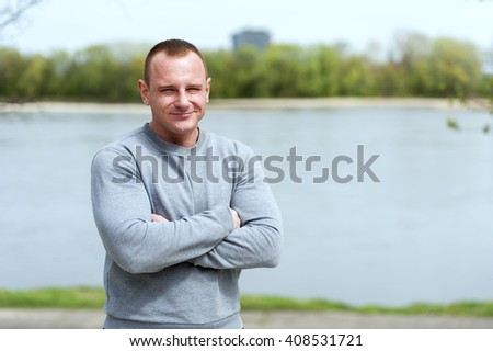 Active man with athletic body and crossed arms, exercise outdoore in park. Fit look. - stock photo