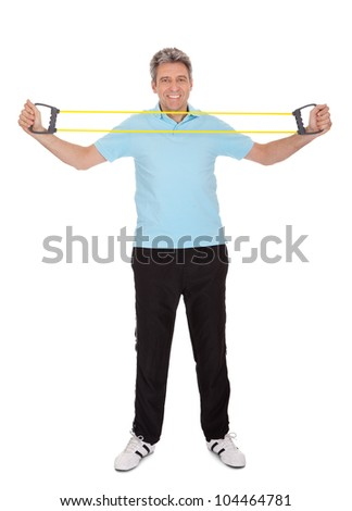 Active mature man doing exercises with expander. Isolated on white