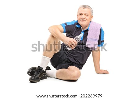 Active mature man holding a water bottle seated on the ground isolated on white background - stock photo
