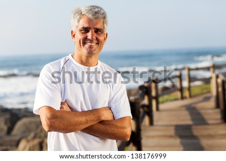 active mid age man in sportswear on the beach - stock photo