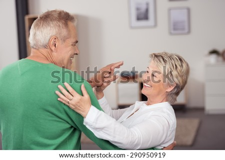 Active Middle Aged Couple Dancing So Sweet While Smiling Each Other at the Living Room Inside their House - stock photo