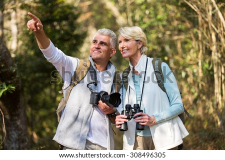 active middle aged couple hiking outdoors in forest - stock photo