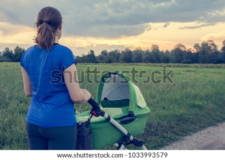 Active mom pushing a stroller at sunset.