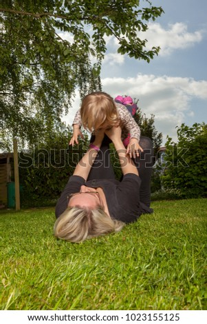 active mother and daughter in the home garden practice some gymnastics