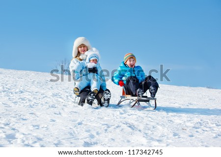 Active mother and kids sleighing down the snowy hill - stock photo