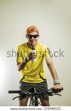Active mountain biker drinking water in studio isolated over white or gray background - stock photo