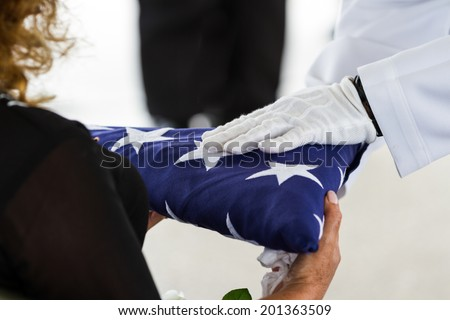 active navy representatives giving the US flag to the widow at a veterans funeral - stock photo