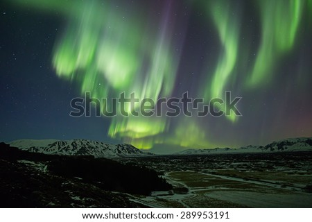 Active northern lights aurora borealis, mountain valley, Thingvellir, Iceland - stock photo