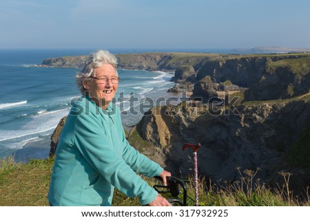 Active old lady pensioner by beautiful coastal view in summer - stock photo