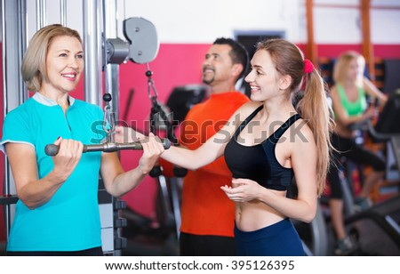 Active positive cheerful people  weightlifting training in modern health club